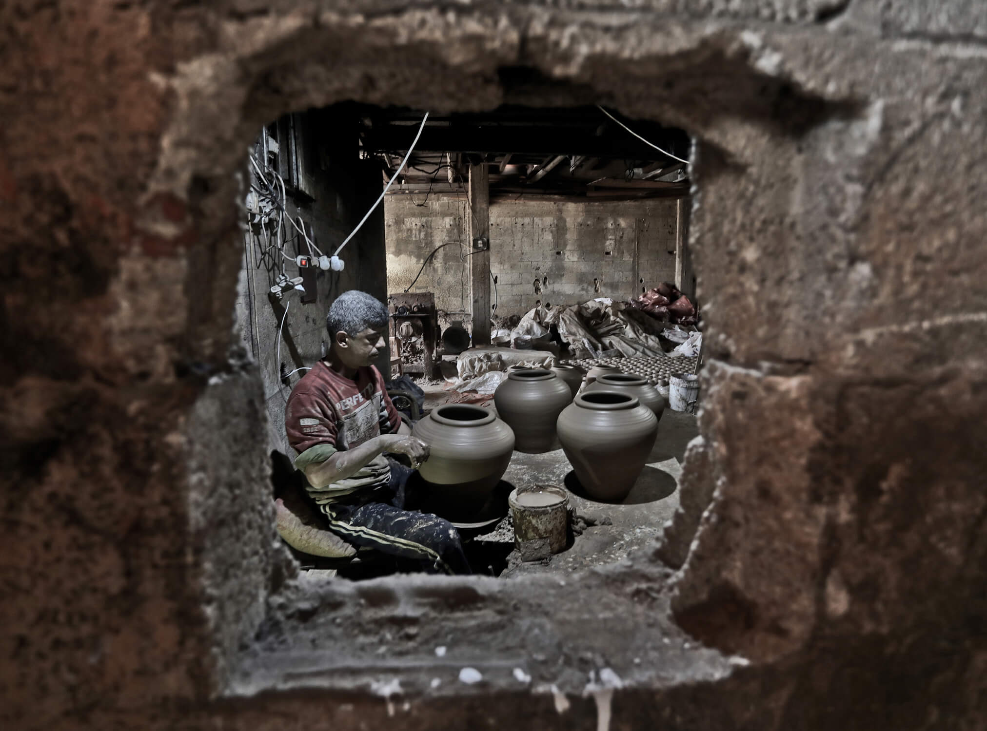 Palestinian handicrafter makes clay pots inside a factory which has been passed down through the generations of his family for centuries