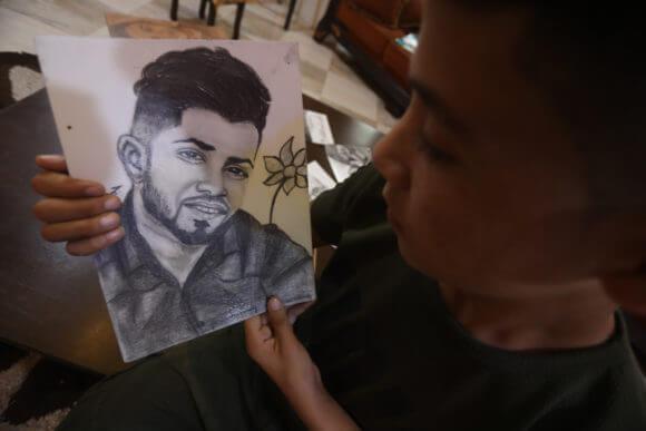 Jamil holding a portrait of his friend, Tamer Abu al-Khair.