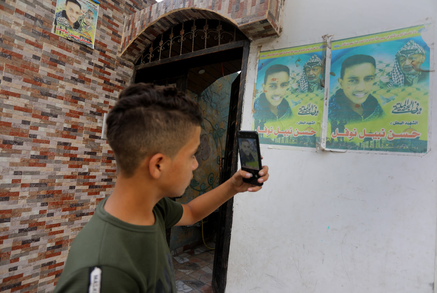 Jamil taking a photo of a poster commemorating Hasan Nawfal.