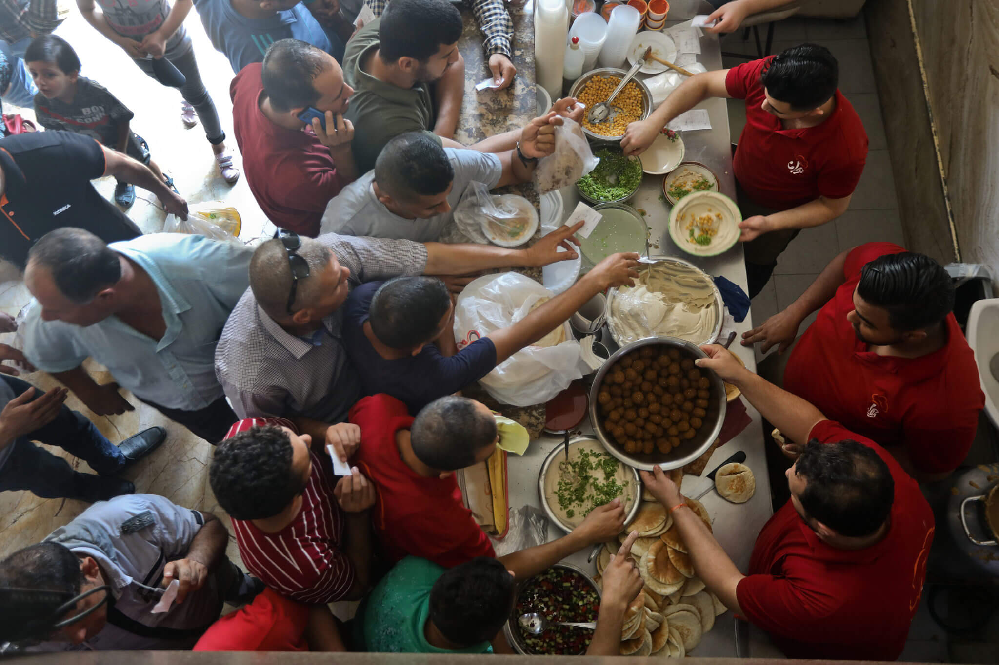 Diners crowd a traditional restaurant to buy falafel, hummus, and mutabbal.