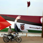 A Palestinian man rides his motorcycle in front of the image of the Emir of Qatar, Sheikh Hamad bin Khalifa Al-Thani, adorn's a barrier where a project funded by Qatar is under construction, in Gaza City on October 21, 2012. (Photo: Ashraf Amra/APA Images)