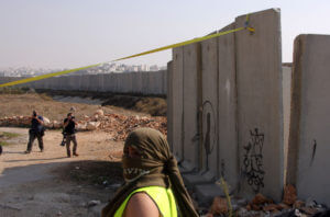 Palestinians mark the fall of the Berlin wall by removing a concrete block from Israel's controversial separation barrier during a protest in the Qalandia refugee camp near the West Bank city of Ramallah, on November 9, 2009. (Photo: by Issam Rimawi/APA Images)