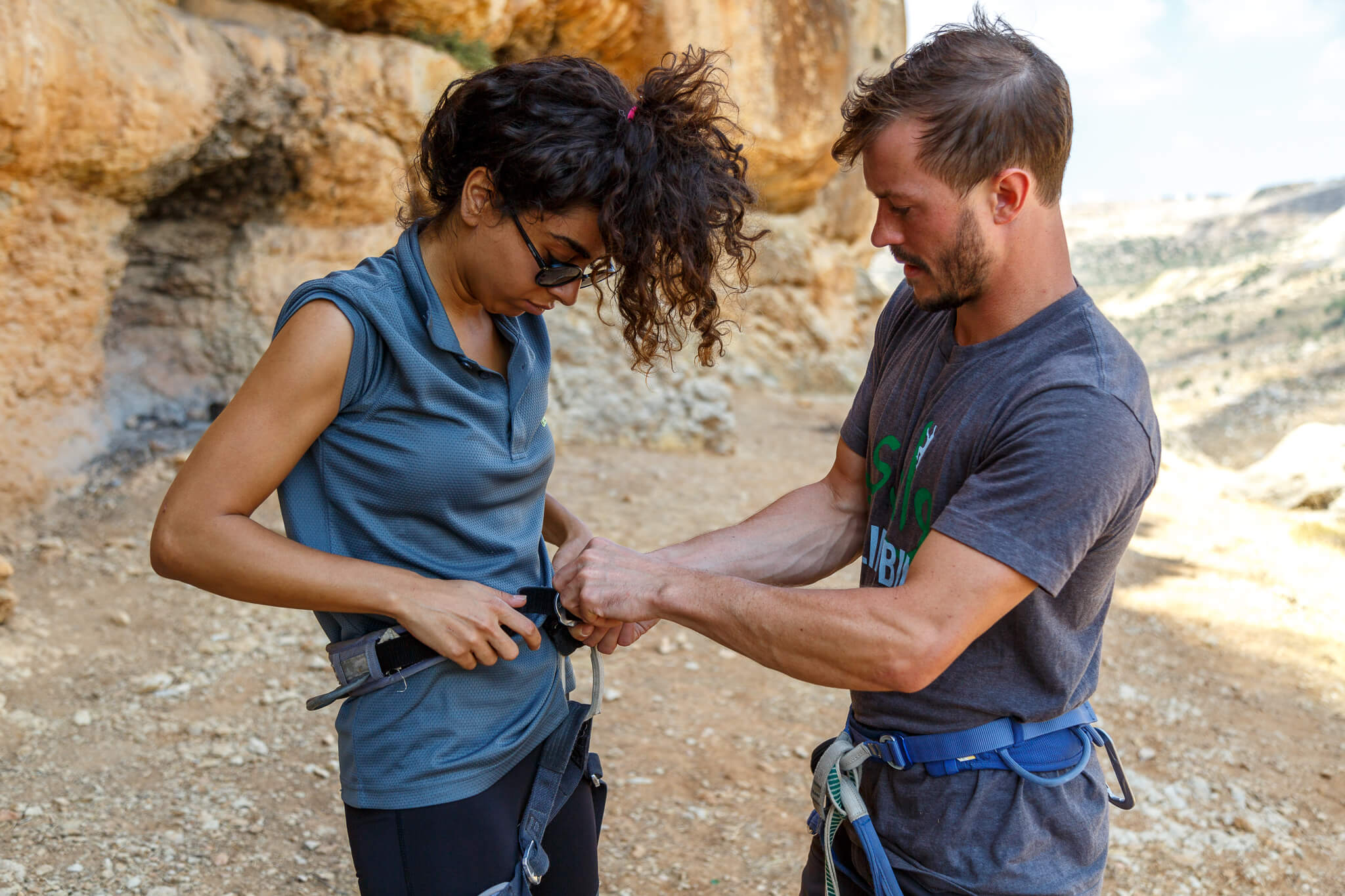 Getting ready to climb, Tyler Myers helps Palestinian climber Aseel into her harness. (Photo: Miriam Deprez)