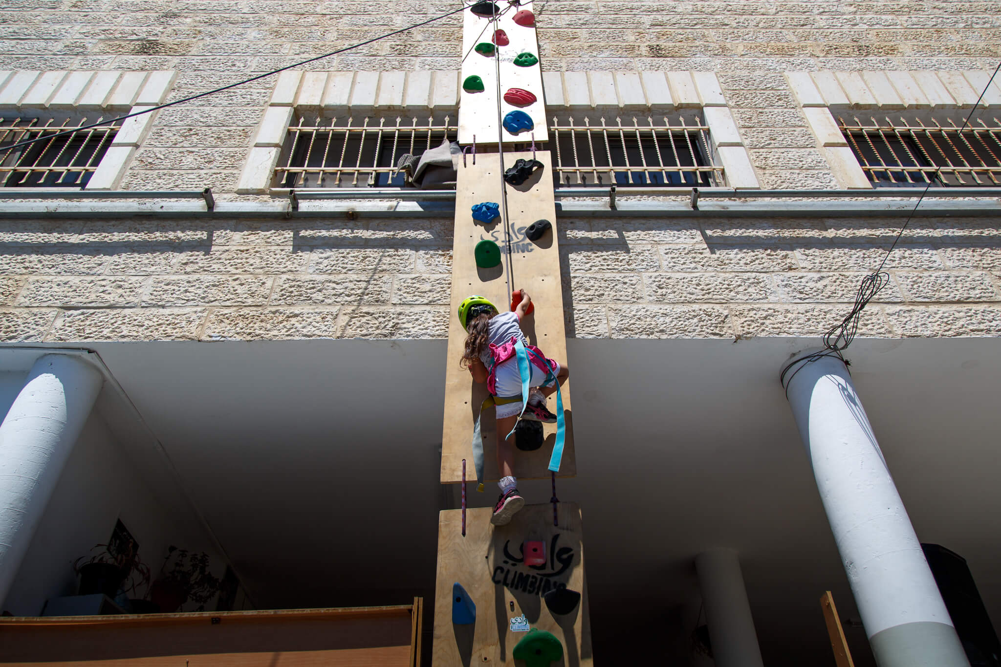 Young girl takes on the 30-foot mobile rock climbing wall at the Shu'fat refugee camp located on the outskirts of Jerusalem. (Photo: Miriam Deprez)