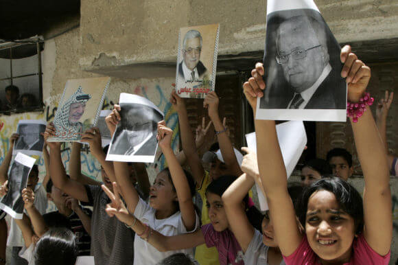 Palestinian children hold posters of President Mahmoud Abbas