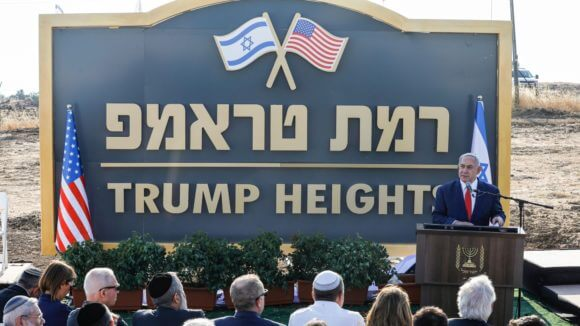 """Prime Minister Benjamin Netanyahu gives a speech before the newly-unveiled sign for the new settlement of """"Ramat Trump"""", or """"Trump Heights"""" in the Golan Heights on June 16, 2019."""