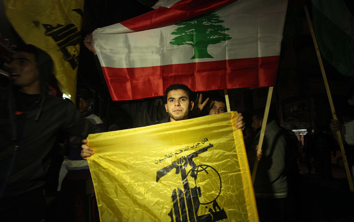 A Palestinian man waves Hezbollah' flag during a rally in Gaza city on January 28, 2015, after two Israeli soldiers and a Spanish peacekeeper were killed in an exchange of fire between Hezbollah and Israel. The soldiers were killed when Hezbollah fired a missile at a convoy of Israeli military vehicles on the frontier with Lebanon. (Photo: Ashraf Amra/APA Images)