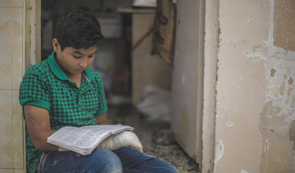 Samer looks at old homework in his own handwriting that he had completed before his injury, in his home in Jabalia refugee camp in the northern Gaza Strip, on May 26, 2019. (Photo: DCIP/Mohammad Ibrahim )