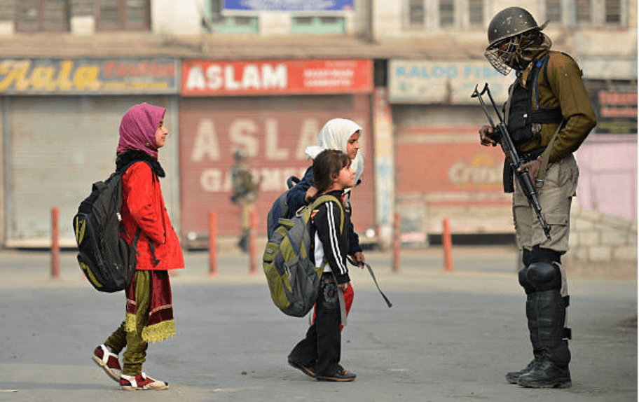 Kashmiri children walk past Indian paramilitary troopers as they stand guard during curfew and restrictions in downtown Srinagar, November 11, 2016. (Photo: Tauseef Mustafa/ AFP/ Getty Images)