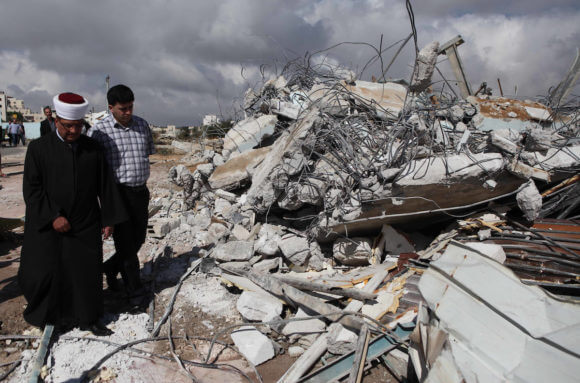 Palestinians inspect the rubble of a dairy factory demolished by Israeli bulldozers, at the al-Rama neighborhood near the West Bank city of Hebron on September 2, 2014. Israeli bulldozers demolish. (Photo: Mamoun Wazwaz/APA Images)