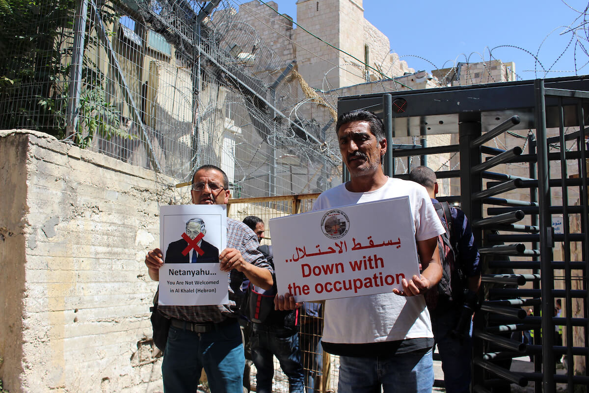 Palestinian protesters hold placards prior to the arrival of the Israeli prime minister to attend a state memorial ceremony at the Ibrahimi mosque, in the West Bank city of Hebron on September 04, 2019. (Photo: Mosab Shawer/APA Images)