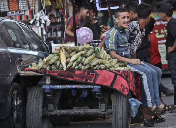 A Gaza young teenager smiles as he sits on the flat bed of a donkey cart used carry corn in al-Nuseirat refugee camp in the Gaza Strip (Photo: Mohammed Asad)