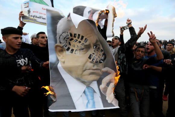 Palestinian protesters deface posters depicting Israeli Prime Minister Benjamin Netanyahu during a protest near the Israel-Gaza border, in Khan Younis in the southern Gaza Strip on November 16, 2018. (Photo: Ashraf Amra/APA Images)