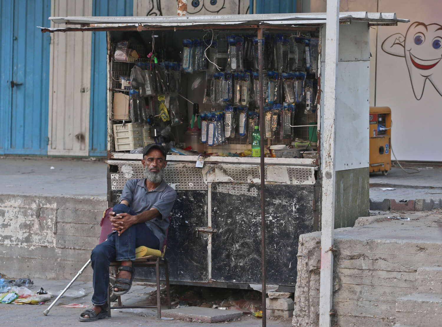 A Palestinian man sits next to his cart where he hangs household items for sell in al-Nuseriat refugee camp in the Gaza Strip (Photo: Mohammed Assad) Mondowiess)