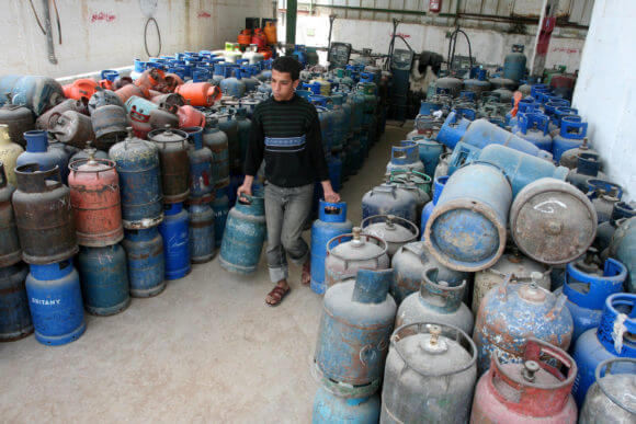 A Palestinian man stands next empty gas canisters at a natural gas station in Gaza City on April 13, 2011, as Gaza Strip suffers from the shortages of natural gas. (Photo: Mohammed Asad)