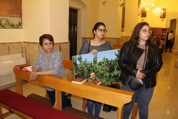 Noura Arbeed holds Samer's picture in church. (Photo: Courtesy of Noura Arbeed)
