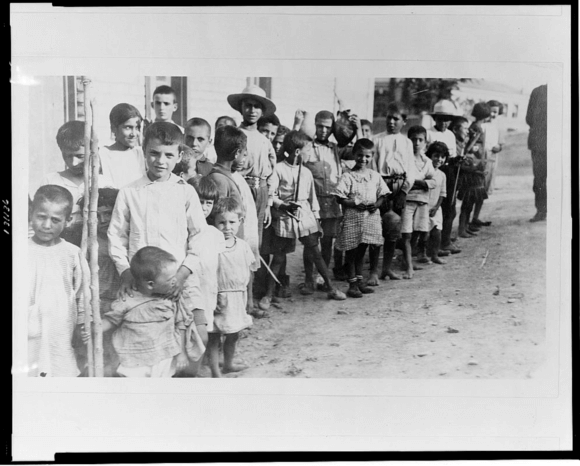 (1923) Greek and Armenian refugee children from Anatolia standing outside one-story building, near Athens, Greece. Greece, 1923. [Photograph] Retrieved from the Library of Congress, https://www.loc.gov/item/2002709161/.