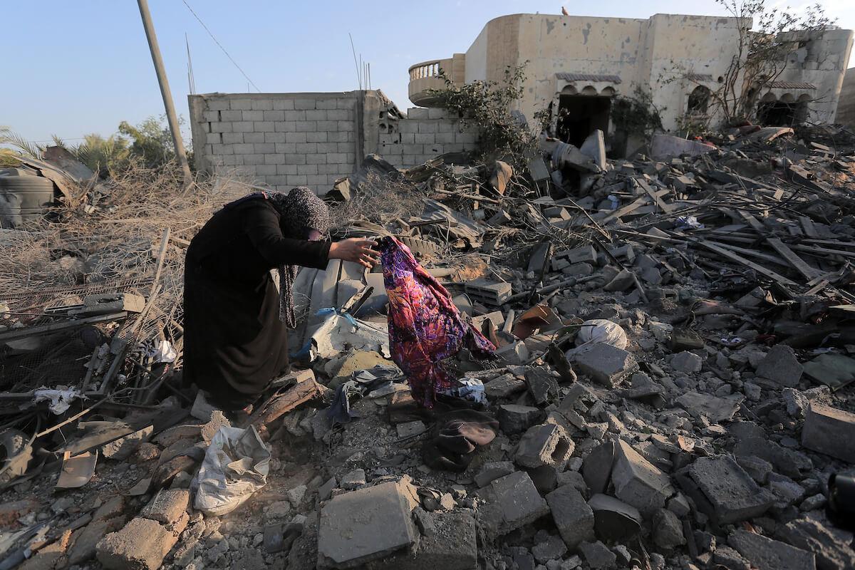 Una donna palestinese raccoglie oggetti da una casa distrutta in un attacco aereo israeliano a Khan Younis nella striscia meridionale di Gaza il 14 novembre 2019. (Foto: Ashraf Amra / APA Images)