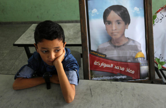 A picture of a Palestinian student, Moath Al Sawarka, who was killed in an Israeli airstrike on the Gaza Strip, is seen on his study seat next to his classmates at a school, in Deir al-Balah, the Gaza Strip on November 16, 2019. Israel said that it targeted Al Sawarka family and killed 8 people by mistake. (Photo: Ashraf Amra/APA Images)