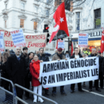 """Supporters of the government of Turkey stage a rally in France. Their sign reads """"The Armenian Genocide is an Imperialist Lie"""""""