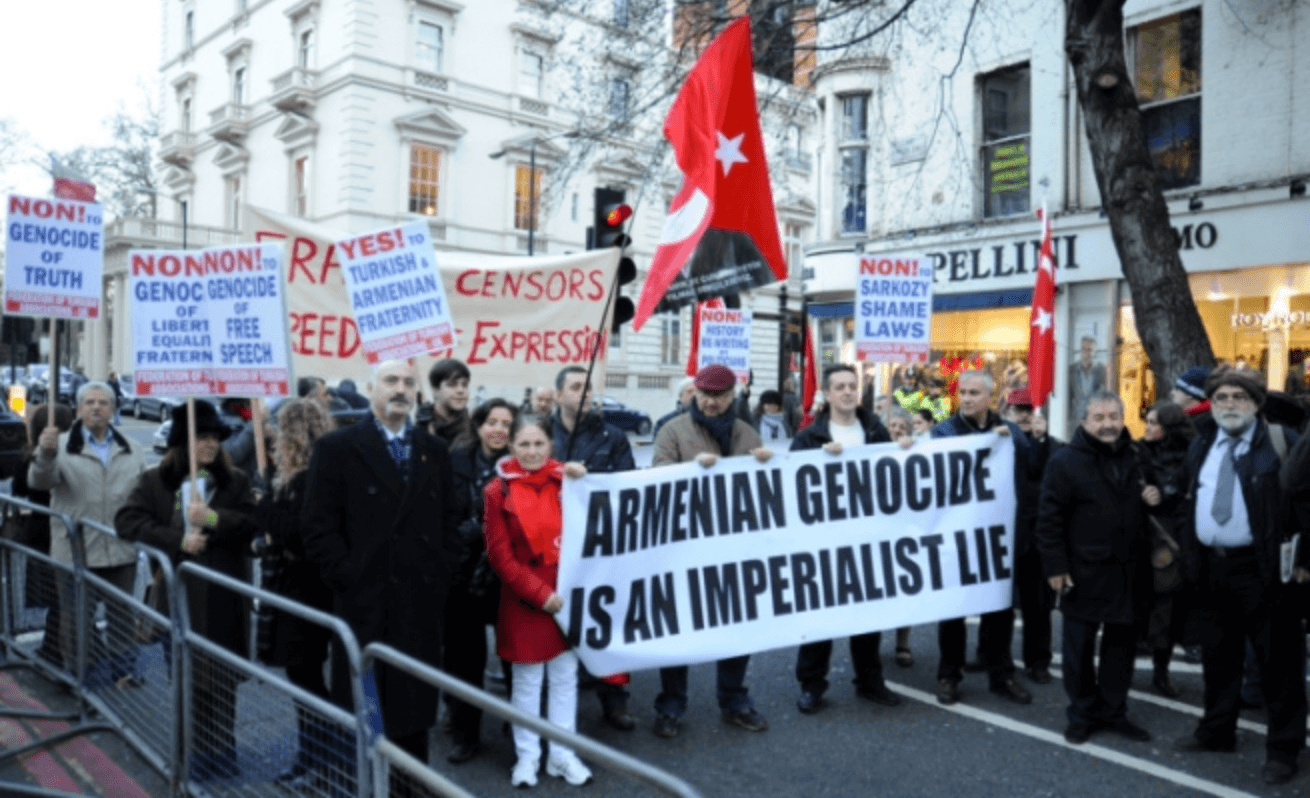 "Supporters of the government of Turkey stage a rally in France. Their sign reads ""The Armenian Genocide is an Imperialist Lie"""
