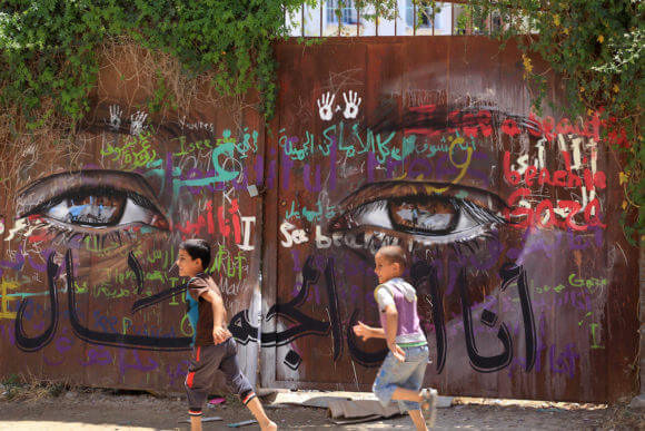 Palestinian children play in front of a gate painted with a mural by the German artist Akot on the walls of houses destroyed during the 2014 war in the Gaza Strip, Gaza City on June 11, 2015. (Photo: Mohammed Asad/APA Images)
