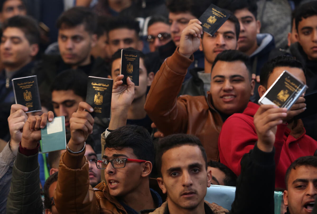 Palestinians hold their passports as they wait for travel permits to cross into Egypt through the Rafah border crossing after it was opened by Egyptian authorities for humanitarian cases, in the southern Gaza Strip December 17, 2017. (Photo: Ashraf Amra/APA Images)