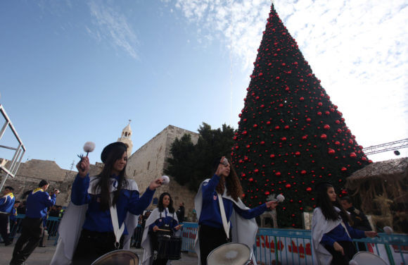 Palestinians celebrate around a Christmas tree at the Manger Square, outside the Church of the Nativity, in the West Bank city of Bethlehem, Sunday, Dec. 24, 2012. (Photo: Issam Rimawi/APA Images)