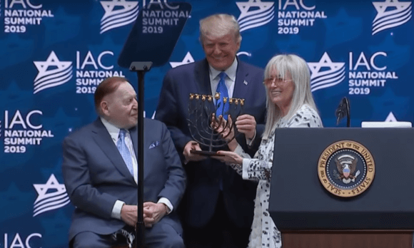 Miriam and Sheldon Adelson present Trump with a menorah, Dec. 7, 2019. Israeli American Council national summit. Screenshot.