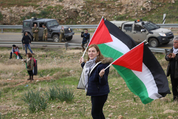 Palestinian woman holds a Palestinian flags during a protest against President Donald Trump's Middle East peace deal and an Israeli declaration to annex the Jordan Valley, near Hamra checkpoint, January 29, 2020. (Photo: Haidi Motola / Activestills)