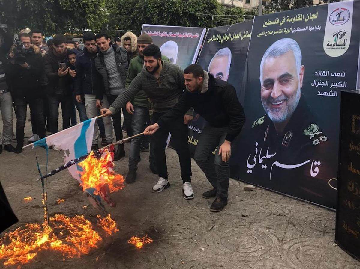 Palestinians in Gaza burn Israeli and American flags outside a mourning tent for Qasem Soleimani (Photo courtesy of Khadija Hmeid)