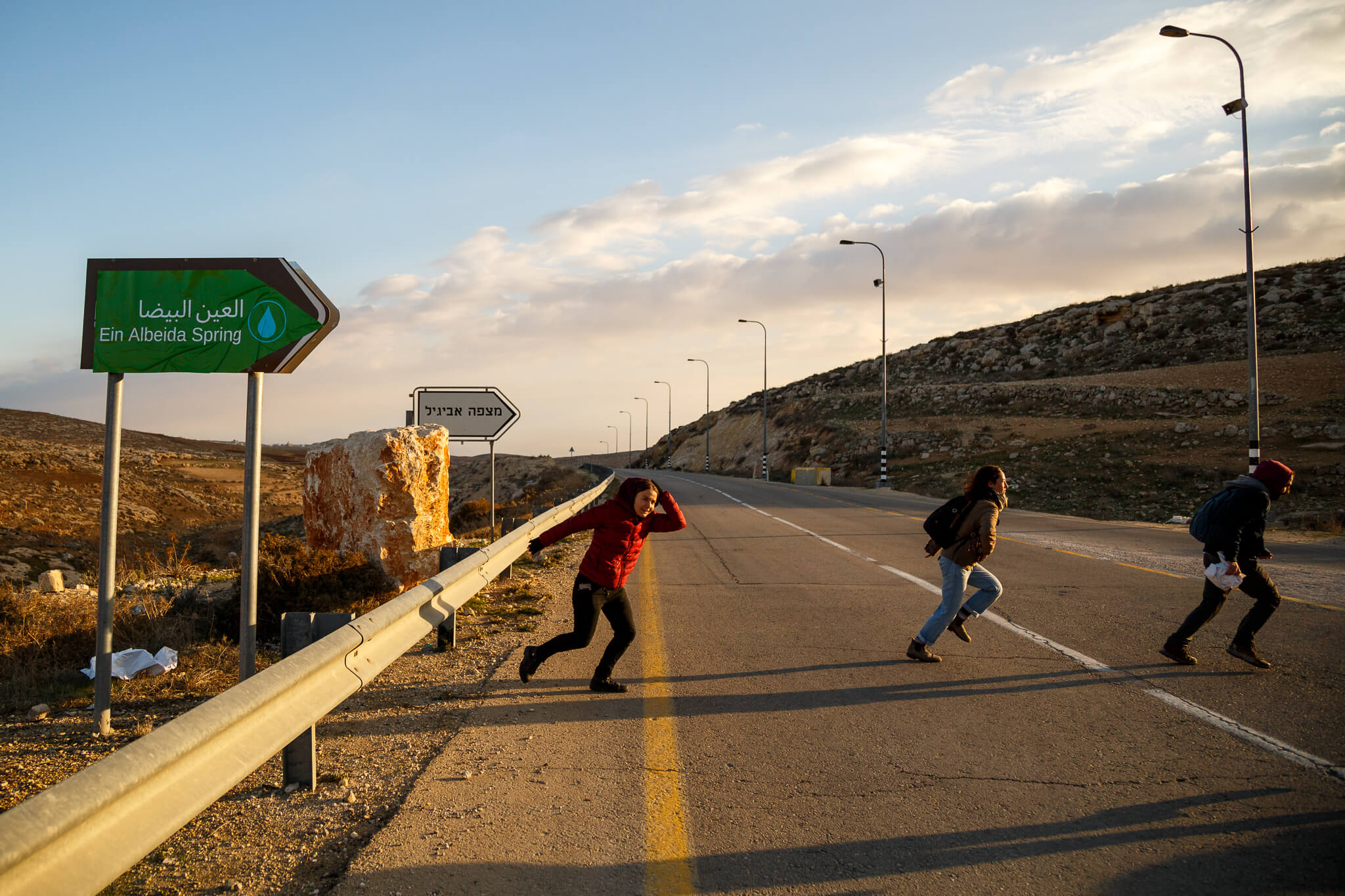Activists dash across a highway after posting a sign in Arabic leading to Ein al-Beida, or Avigayil Spring. (Photo: Miriam Deprez)