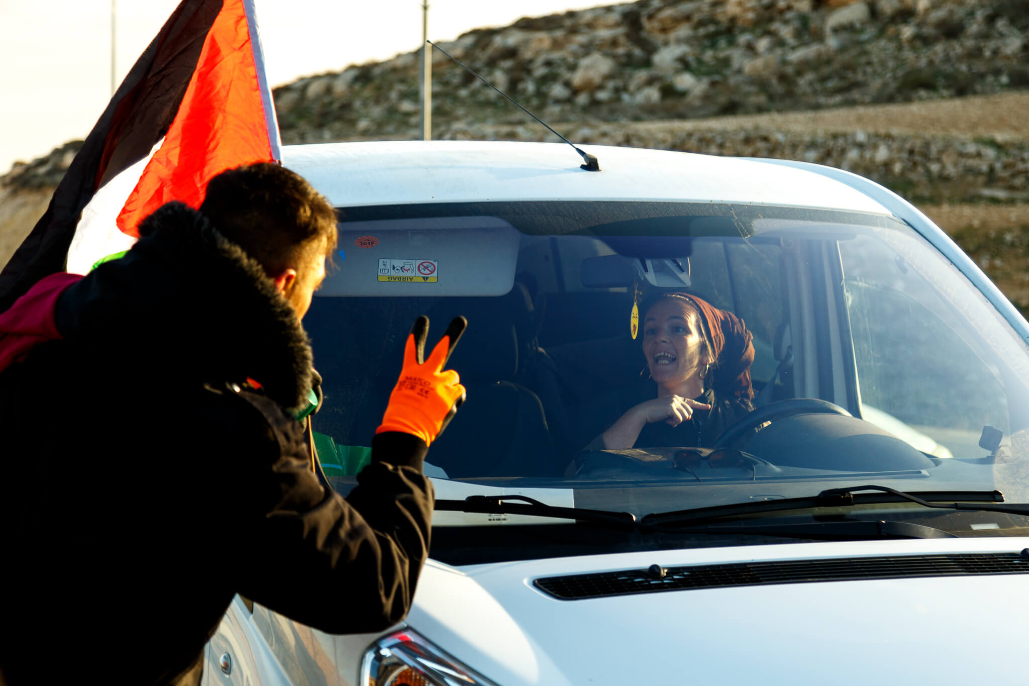 Israeli setter drives by Palestinians. (Photo: Miriam Deprez)