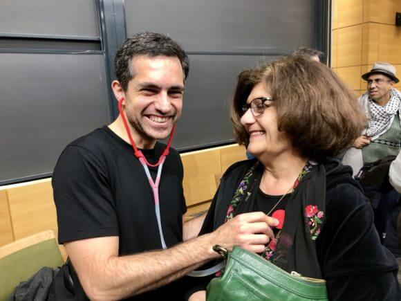 Dr. Tarek Loubani demonstrating his stethoscope made by a 3 D printer on a conference participant. (Photo: Hubert Murray)