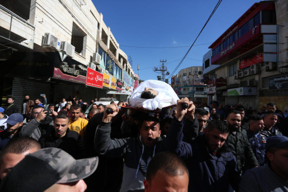 Palestinian policemen carry the body of their colleague Tareq Badwan, who was shot dead by Israeli forces, during his funeral in the West Bank city of Jenin, February 6, 2020. (Photo: Shadi Jarar'ah/APA Images)