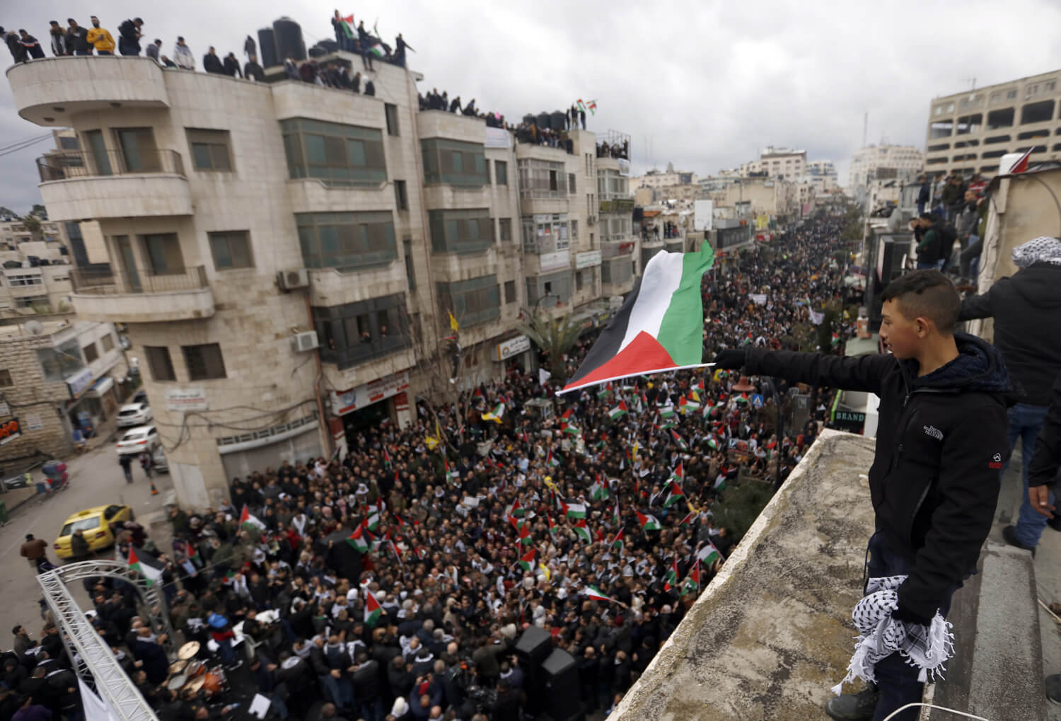 "Palestinian protesters wave national flags during a rally in support of Palestinian President Mahmoud Abbas and against US President Donald Trump's ""Deal of the Century"" in the West Bank city of Ramallah, on February 11, 2020. Photo by Oday Deybes/ WAFA"