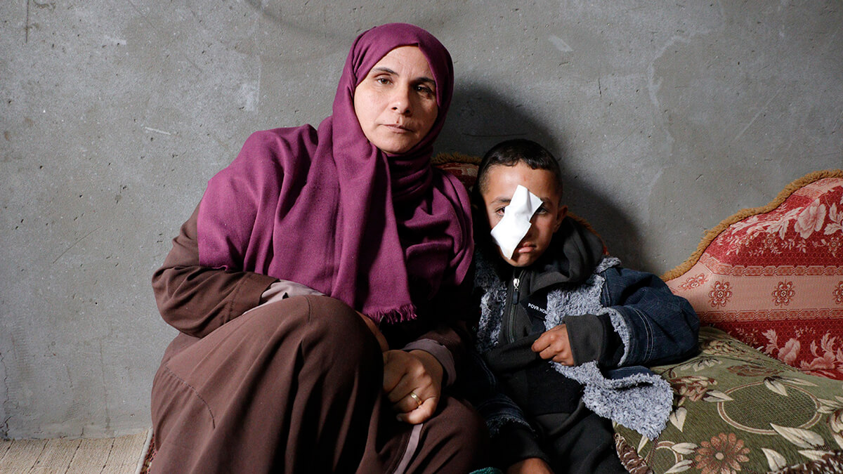 Muhammad Abu Raidah, 10, with his mother Jihan. (Photo: B'Tselem)