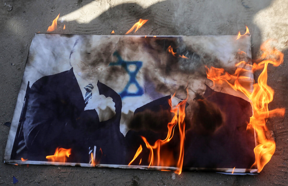 Palestinian protesters burn pictures depicting President Donald Trump and Israeli Prime Minister Benjamin Netanyahu during a protest against the Trump administration's peace plan, in Khan Yunis in the southern of Gaza Strip on January 31, 2020. (Photo: Ashraf Amra/APA Images)