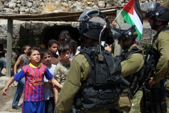Israeli soldiers confront Palestinian children during a demonstration against Israel's separation barrier in the West Bank village of Nabi Saleh near Ramallah, Friday, June 29, 2012. (Photo: Issam Rimawi/APA Images)