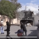 Still from video of Israeli military bulldozer attacking protesters during an anti-settlements protest in the village of Kufur Qaddoum.