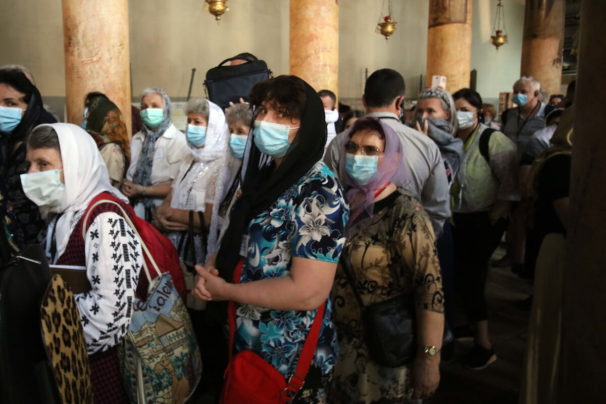 Foreign tourists wearing masks as a preventive measure against the coronavirus during a visit to the Church of the Nativity, in the West Bank city of Bethlehem on March 05, 2020. (Photo: Abedalrahman Hassan/APA Images)