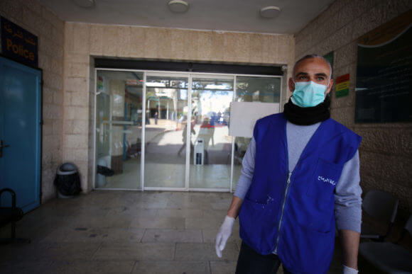 A Palestinian man wears a mask as a preventive measure against the Coronavirus stands outside Beit Jala governmental hospital, in the West Bank city of Bethlehem on March 5, 2020. The Palestinian health ministry called for local churches, mosques and other institutions to close after a number of suspected cases of coronavirus COVID-19 at a hotel in the Holy Land city of Bethlehem. (Photo: Abedalrahman Hassan/APA Images)