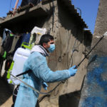 A Palestinian worker wearing protective gear disinfects streets as a preventive measure amid fears of the spread of the coronavirus, at al-Shati refugee camp in Gaza City on March 16, 2020. (Photo: Ashraf Amra/APA)