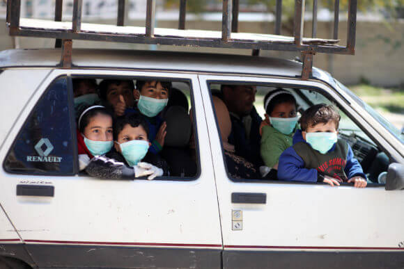 Palestinian children wear face masks in Gaza City early on March 22, 2020. Authorities in Gaza confirmed the first two cases of novel coronavirus on Saturday, identifying the individuals as Palestinians who had travelled to Pakistan and were held in quarantine. (Photo: Mahmoud Ajjour/APA Images)