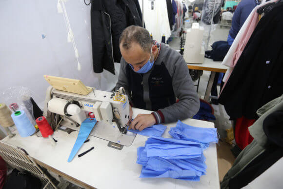 Palestinian workers sew protective masks and medical clothing at the UniPal 2000 factory in the Karni industrial zone, in Gaza City on March 25, 2020. Production of face masks in factories has increased recently amid concerns over the spread of the novel coronavirus. (Photo: Ashraf Amra/APA Images)