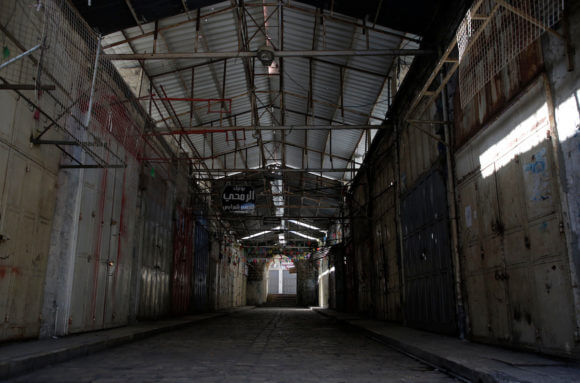 Shops are shuttered in an outdoor market after Palestinians are ordered to stay at home as a precaution against the spread of the coronavirus, in the West Bank city of Nablus, on March 25, 2020. (Photo: Shadi Jarar'ah/APA Images)