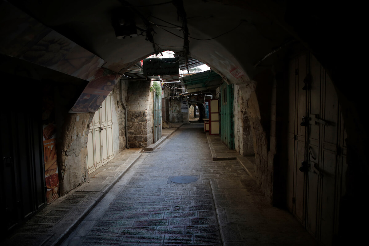 Closed shops in the West Bank city of Nablus, which is under a home confinement order as a precaution against the spread of the coronavirus disease (COVID-19), March 25, 2020. (Photo: Shadi Jarar'ah/APA Images)