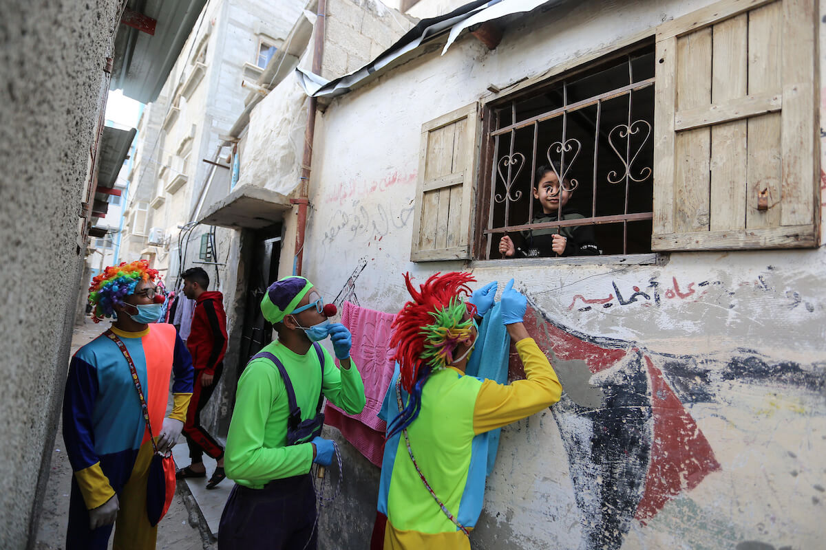 Palestinian clowns wear face masks as they visit children isolating in their homes as a preventive measure amid fears of the spread of the novel coronavirus in Khan Yunis in the southern Gaza Strip on April 01, 2020. The United Nations has warned that a COVID-19 outbreak in Gaza could be disastrous, given the high poverty rates and weak health system in the coastal strip under Israeli blockade since 2007. (Photo: Ashraf Amra/APA Images)