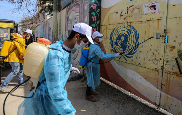 Palestinian workers spray disinfectant outside an UNRWA school as a preventive measure amid fears of the spread of the coronavirus, in Deir Al Balah in the Gaza Strip, on April 2, 2020. (Photo: Ashraf Amra/APA Images)