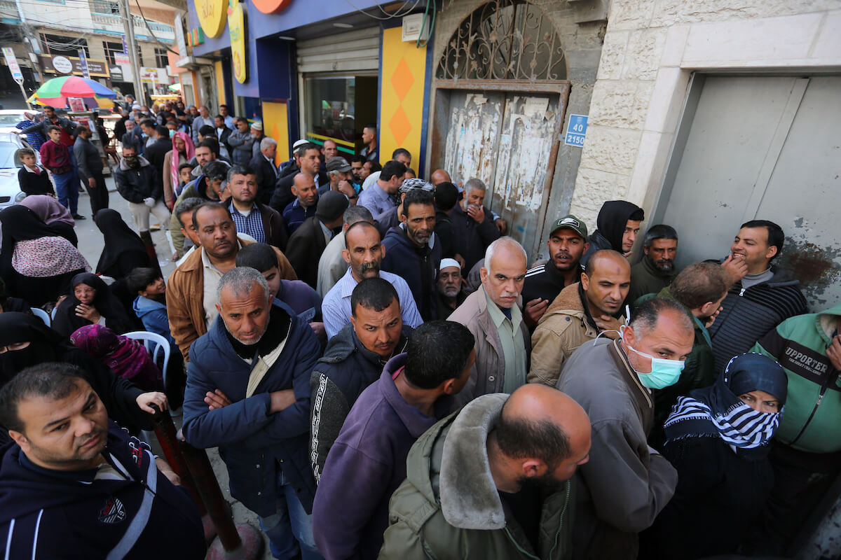 Palestinian Authority employees wait to withdraw cash from an ATM outside a Bank of Palestine branch in Khan Younis in the southern Gaza Strip, on April 2, 2020. (Photo: Ashraf Amra/APA Images)